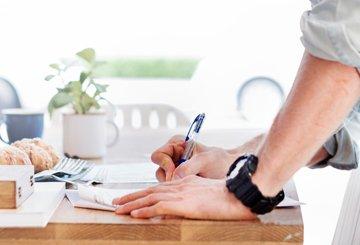 Man skriver på papper